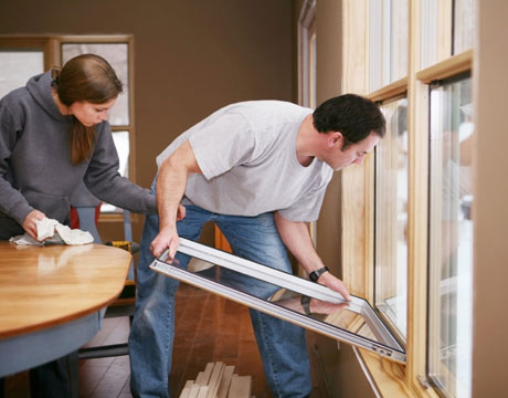 a man and woman install storm windows