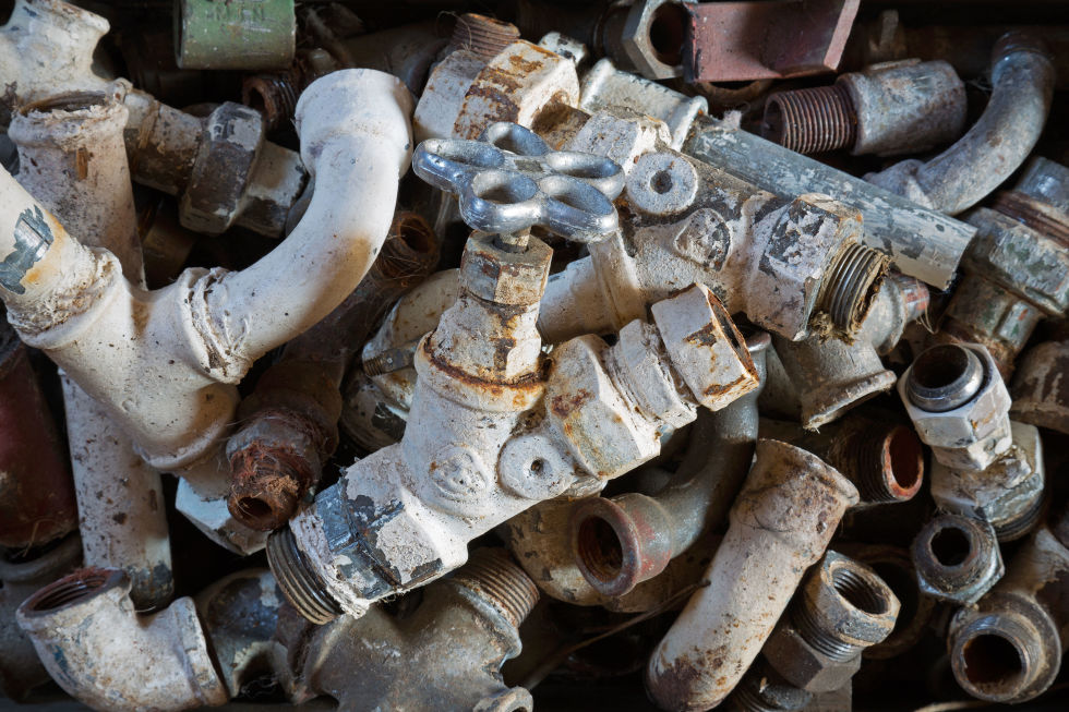 An old pile of rusted pipe ends and fittings destined for the junk pile.